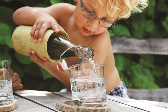 Young blonde boy with glasses pouring water from a glass jug